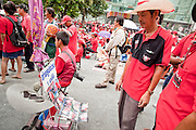 17 APRIL 2010 - BANGKOK, THAILAND: A Red Shirt snapshot vendor takes pictures of people at the Red Shirt rally, then sells them prints he makes with a small Canon printer. A whole economy has sprung up around the Red Shirt camp with vendors selling everything from snacks and meals to mats (that they sit on) to fans, hats and Red Shirt souvenirs. The Red Shirts continue to occupy Ratchaprasong Intersection an the high end shopping district of Bangkok. They are calling for Thai Prime Minister Abhisit Vejjajiva to step down and dissolve the parliament. Most of the Red Shirts support ousted former Prime Minister Thaksin Shinawatra.   PHOTO BY JACK KURTZ
