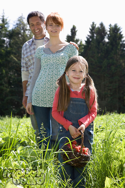 Parents and daughter (5-6) in strawberry field portrait