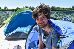 "© Licensed to London News Pictures. 30/06/2018. LONDON, UK.  Darius Platt-Vowles from Gloucestershire poses in his tent in Wimbledon Park.  He is the first in ""The Queue"" for premium tickets, having arrived on Thursday 28 June, four days before the Wimbledon tennis championships are to begin on 2 July.  He hopes to be able to obtain tickets to centre court to see his idol, Roger Federer.  Photo credit: Stephen Chung/LNP"