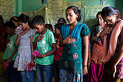 Members of the Kishuri Sachetana Child Club sign the Nepal national anthem before a meeting in their activity center in Thahuri Tole, Chhinchu, Surkhet district, Western Nepal, on 1st July 2012. These Child Clubs, supported by the government, Save the Children and their local partner NGO Safer Society, advocate for child rights and against child marriages and use peer support and education to end child marriages and raise awareness. Photo by Suzanne Lee for Save The Children UK