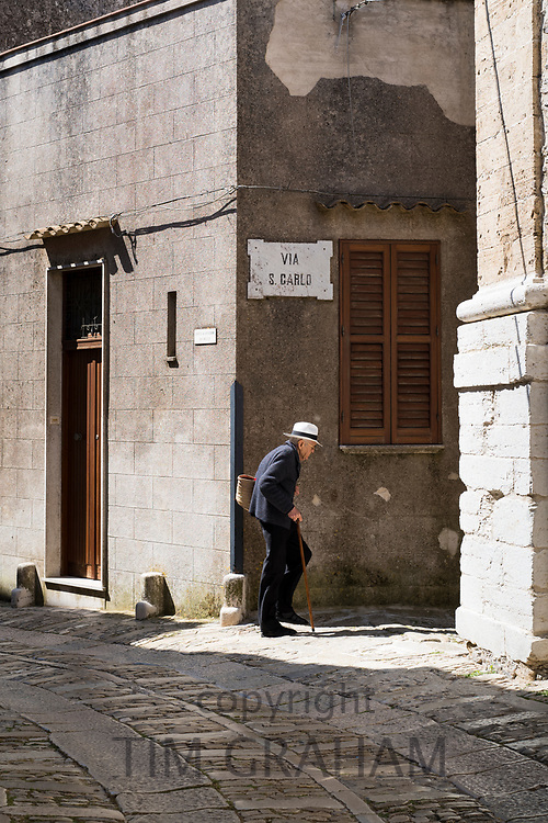 Street scene of elderly man with walking stick and shopping bag in cobble stones alleyway in Erice, Sicily, Italy