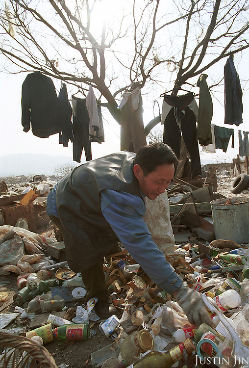 A man sorts rubbish in front of his clothes which are being hanged to dry at a garbage dump in Beijing...Between 50-100 Chinese from a small village in southwestern China's Sichuan province live and work here, one thousand miles away from home. They are part of a cooperative selling scraps and wastes to local farmers and factories...They look for bits of wire, bottles and plastics that they can re-sell. They earn about 300 yuan (US$36) a month per person, which is low by urban standards but is about 10 times as much as wages at home in Sichuan...Picture taken March 1999.Copyright Justin Jin