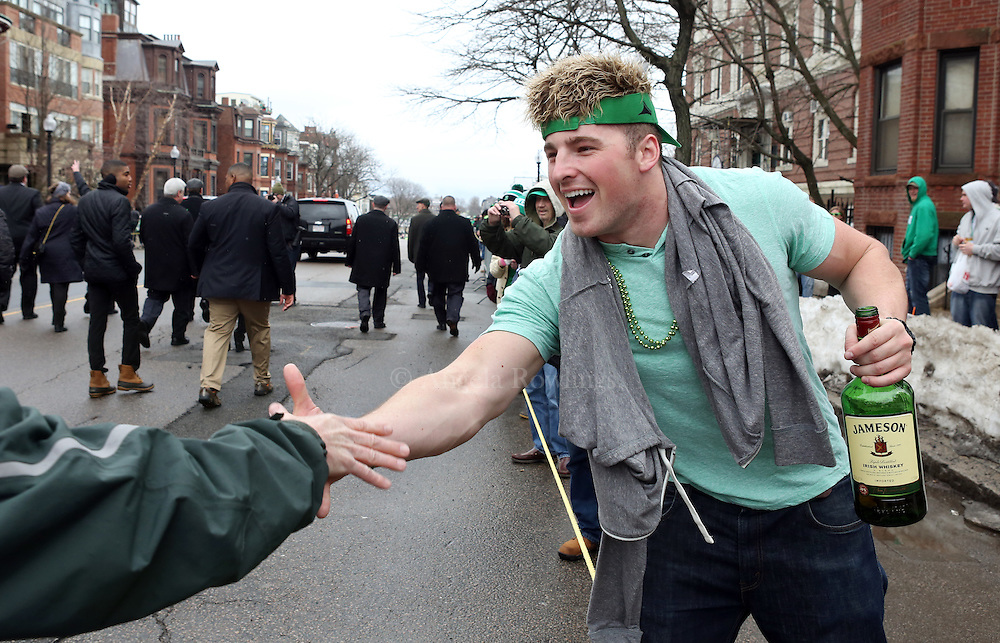 (Boston, MA - 3/15/15) Tim Joy [identified himself as BC football player] greets a marcher during the St. Patrick's Day Parade in South Boston, Sunday, March 15, 2015. Staff photo by Angela Rowlings.