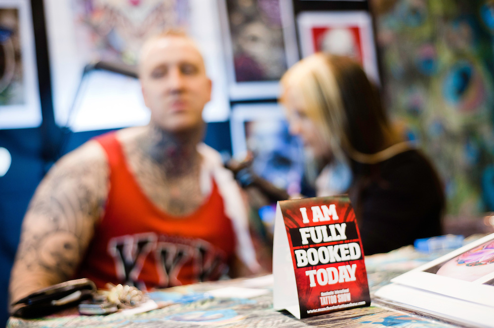 Manchester, UK - 4 August 2012: a sign reading 'I am fully booked today' on the table of an artist tattoing a visitor during the Manchester Tattoo Show, one of the most popular conventions of the UK tattoo community.