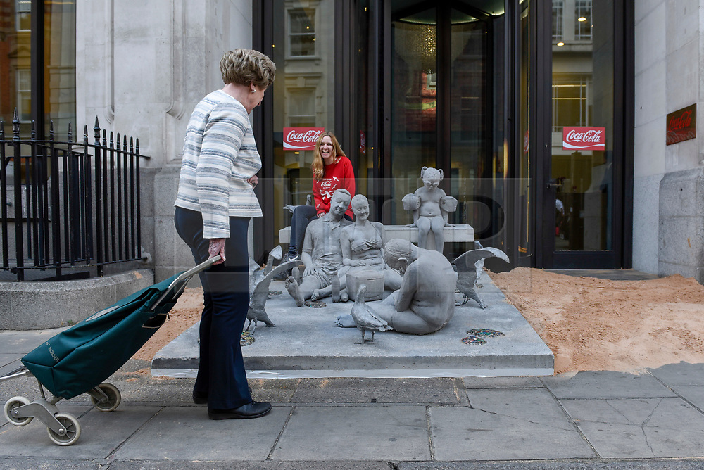 """© Licensed to London News Pictures. 10/04/2017. London, UK.  A sculpture by artist James de Caires Taylor, depicting a family on a beach, is installed by Greenpeace in front of the entrance of Coca-Cola's London headquarters on Wimpole Street as part of the campaign called """"Don't let Coke choke our oceans"""".  The campaign highlights the negative environmental impact of plastics in the oceans as well as Coca-Cola's increased use of throwaway plastics as opposed to recycled plastics.   Photo credit : Stephen Chung/LNP"""
