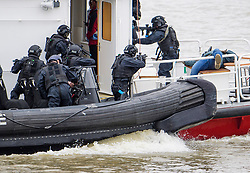 © Licensed to London News Pictures. 19/03/2017. London, UK. A man playing a terrorist (right) is seen pretending to be dead as , Anti-terror Police board a tourist boat, taken hostage by people playing armed terrorists, in an ant-terror training exercise takes place on The River Thames in  London. It is the first time that an exercise of this type has taken place on the river. Photo credit: Ben Cawthra/LNP