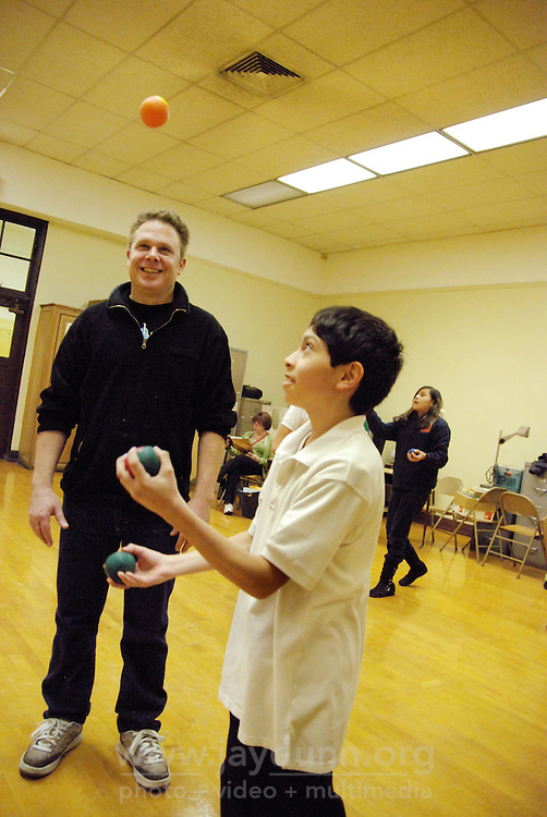 "USA, Chicago, IL, December 12, 2009.  Instructor Douglas Grew checks a student's juggling progress. Students in the ""At-Risk After School Program"" at Maria Saucedo Scholastic Academy receive training in basic physics principles through an innovative new program called ""Circus Galactica"" put on by Pros Arts, a non-profit organization founded in 1978 by professional artists dedicated to the Pilsen/Little Village communities. In a residency that directly integrates science and art, veteran circus performers Douglas Grew and Paul Lopez bring the importance of ""balance, focus and presentation"" into hands-on lessons about gravity, inertia, and the dynamics of objects in motion. Photo for Hoy by Jay Dunn."