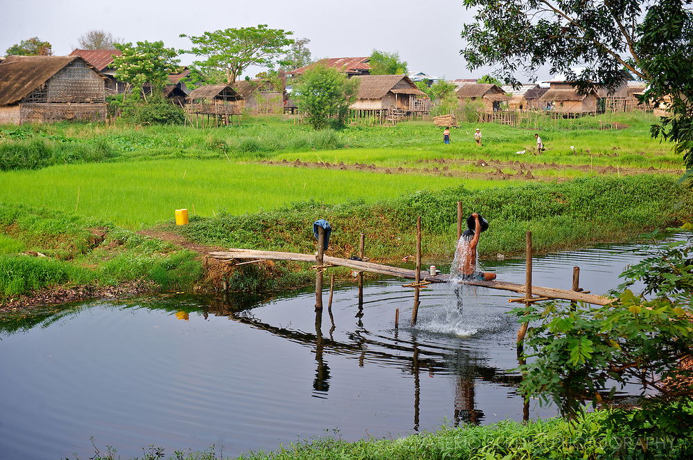 Man takes a shower on a bridge over a canal close to his village.