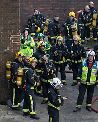 © Licensed to London News Pictures. 14/06/2017. London, UK. Firemen and women look up directly under Grenfell Tower on the Lancaster West Estate -  scene of a huge fire in west London. The blaze engulfed the 27-storey building with 200 firefighters attending the scene. A number of fatalities have been reported. Photo credit: Peter Macdiarmid/LNP
