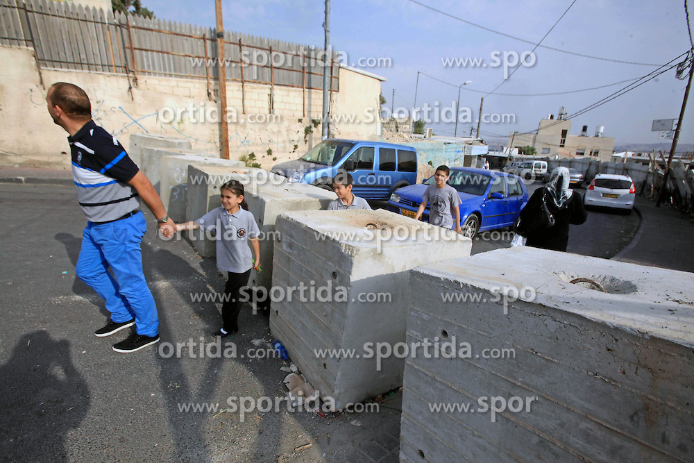 19.10.2015, Jerusalem, ISR, Gewalt zwischen Pal&auml;stinensern und Israelis, im Bild Kontrollen der Israelischen Sicherheitskr&auml;fte im Pal&auml;stinenser Gebiet // Palestinians walk between cement blocks at a newly erected checkpoint in Jerusalem's neighborhood of Jabal al-Mokaber on October 19, 2015. Israeli police began erecting a wall in east Jerusalem to protect a Jewish neighbourhood subject to firebomb and stone attacks launched from an adjacent Palestinian village, Israel on 2015/10/19. EXPA Pictures &copy; 2015, PhotoCredit: EXPA/ APAimages/ Mahfouz Abu Turk<br /> <br /> *****ATTENTION - for AUT, GER, SUI, ITA, POL, CRO, SRB only*****