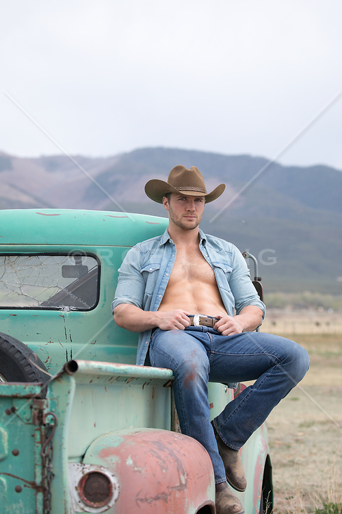 hot cowboy with an open shirt sitting on a truck with views of a mountain