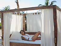 Mid-adult woman lying on bed on beach