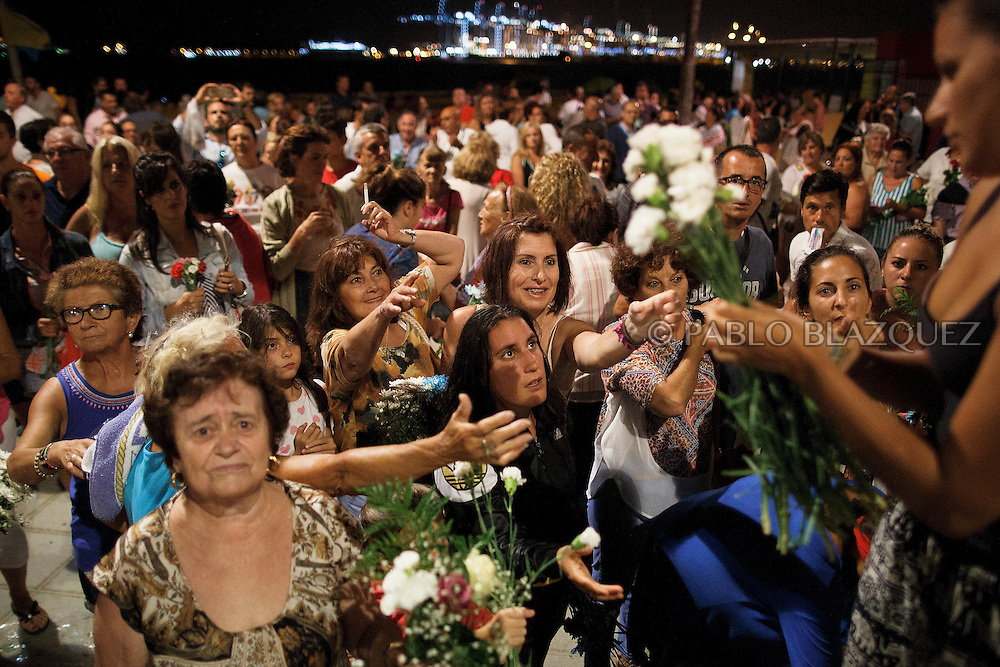 15/08/2016. Worshippers wait for flowers from the Virgin of Palm's pedestal before it goes back to the sea during the yearly Virgin of Palm maritime pilgrimage at El Rinconcillo beach on August 15, 2016 in Algeciras, Spain. The Our Lady of Palm maritime pilgrimage in Algeciras dates back to 1975 and takes place annually when fishermen rescue the submerged virgin from the deep sea. Worshippers amid thousands of visitors await its arrival at the Rinconcillo beach. The devotion for the Virgin of Palm comes from the seventeenth century when a ship coming from Italy docked at Algeciras port to wait out bad weather. According to legend, once the crew of the ship removed a box with an image of the Virgin from its cargo the weather turned and the sea's tides were calmed. (© Pablo Blazquez)
