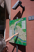 Under the gaze of CCTV, tourists point to a map in the northern Italian south Tyrolean city of Bozen-Bolzano.