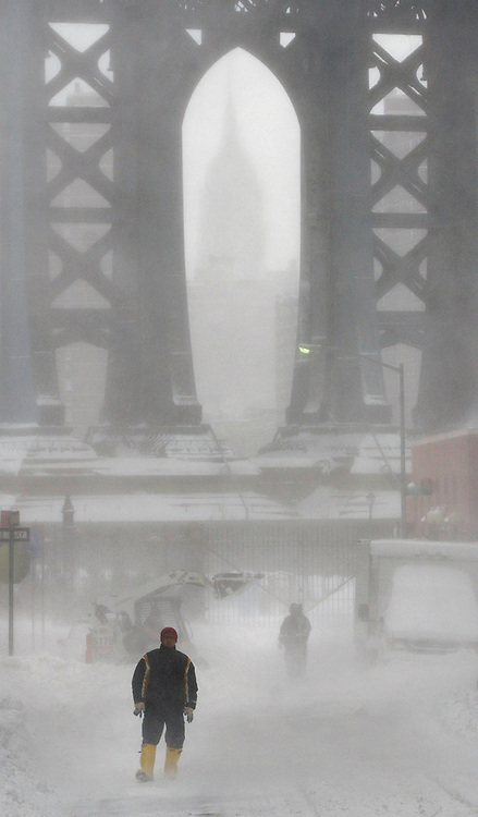 A pedestrian is seen walking on a snow covered street with the Empire State Building seen through the base of Manhattan bridge in the background in Brooklyn, NY Sunday, 23 January 2005. A winter storm dumped over a foot of snow on the Eastern United States, causing nearly 500 flights to be canceled Sunday morning at the New York metropolitan area's Newark, Kennedy and LaGuardia airports.