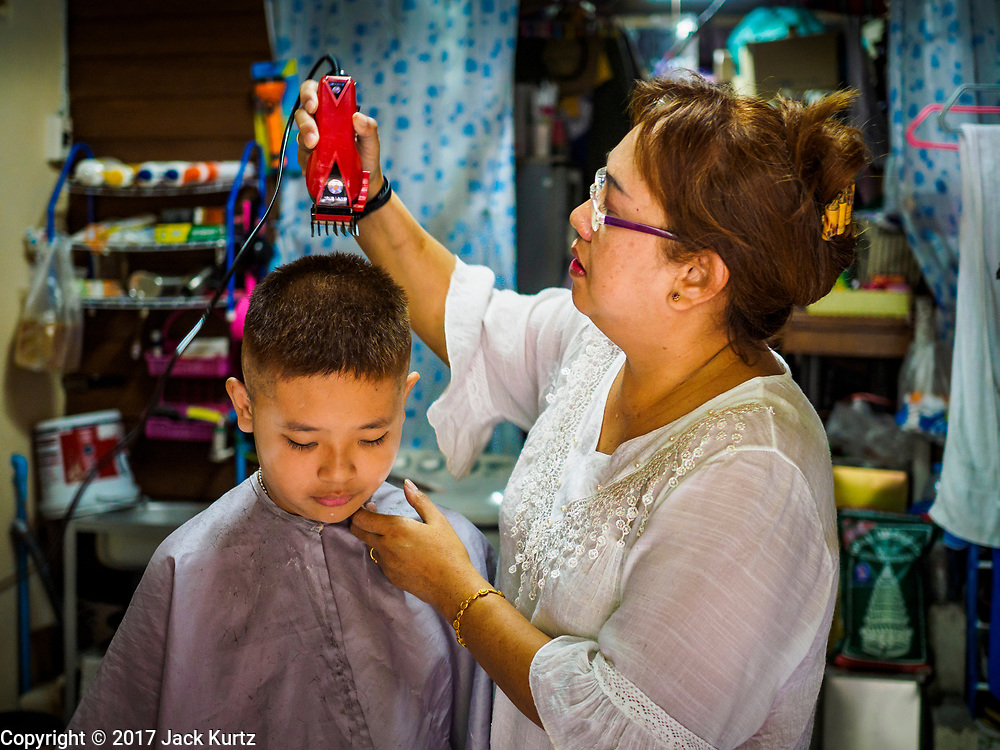 07 APRIL 2017 - BANGKOK, THAILAND:  A woman gives her son a haircut in their home in Pom Mahakan. The final evictions of the remaining families in Pom Mahakan, a slum community in a 19th century fort in Bangkok, have started. City officials are moving the residents out of the fort. NGOs and historic preservation organizations protested the city's action but city officials did not relent and started evicting the remaining families in early March.             PHOTO BY JACK KURTZ