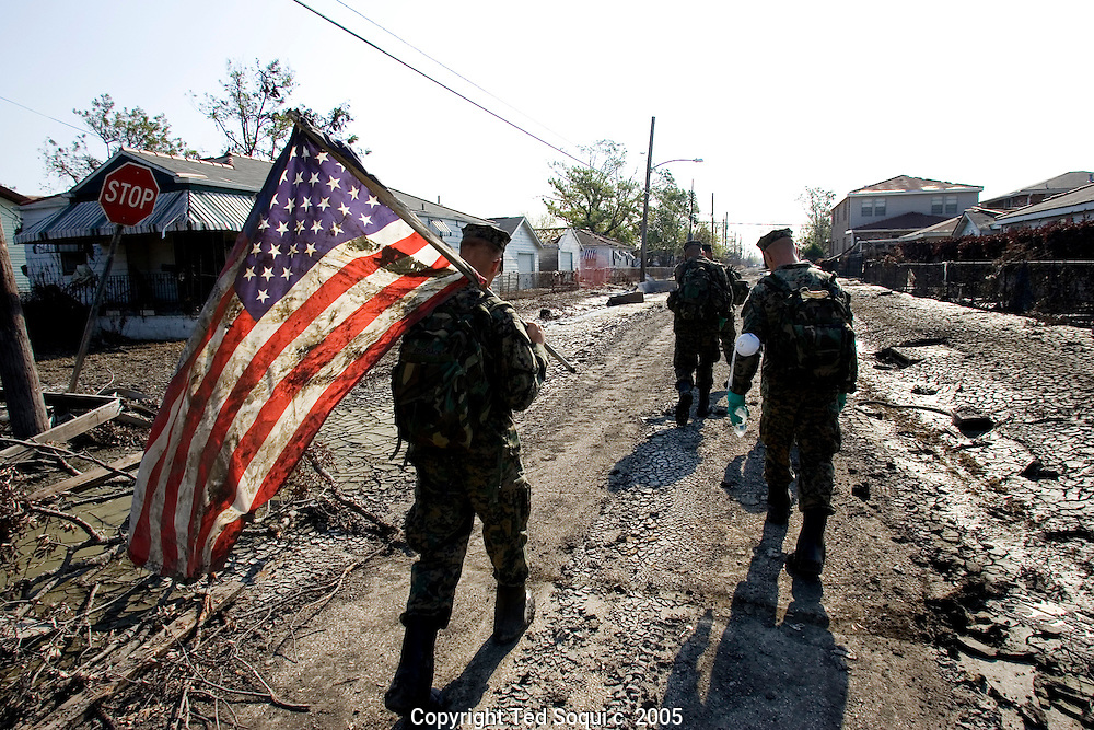 The Hurricane Katrina aftermath In New Orleans..Members of the Marine Corps. 1st battalion 8th division out of No. Carolina holding a muddy US flag they rescued from a flood ravaged home. 9th ward district of New Orleans. This area is primarily poor and has a large population of black Americans.