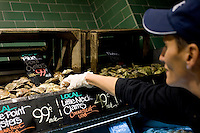 9 July, 2008. New York, NY. Amy Jo Dimaglio (41, Coordinator of the seafood program) picks some oysters to shuck at the shucking station of the new Whole Foods that opened in Tribeca today, on July 9th 2008. The shucking station for oysters and clams is a new feature of the Whole Foods Market.<br /> <br /> ©2008 Gianni Cipriano for The New York Times<br /> cell. +1 646 465 2168 (USA)<br /> cell. +1 328 567 7923 (Italy)<br /> gianni@giannicipriano.com<br /> www.giannicipriano.com