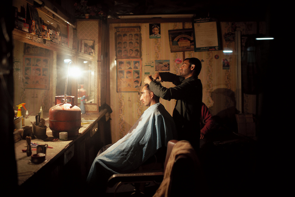 A customer has his hair trimmed in a barber shop during a power cut in the town of Skardu, Gilglit-Baltisan Province, Pakistan on October 25, 2012
