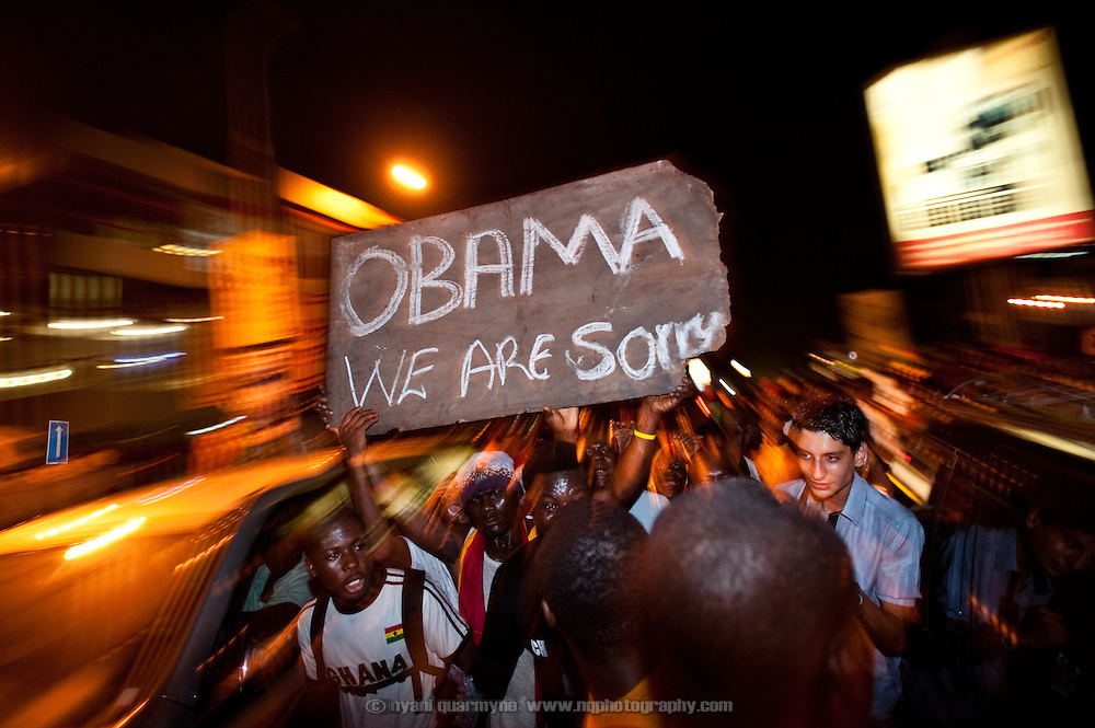 """A crowd bearing a sign reading """"Obama We Are Sorry"""" marches down Oxford Street in Accra, Ghana as Ghanaians took to the streets to celebrate their win over the USA on 26 June 2010 during the FIFA World Cup."""