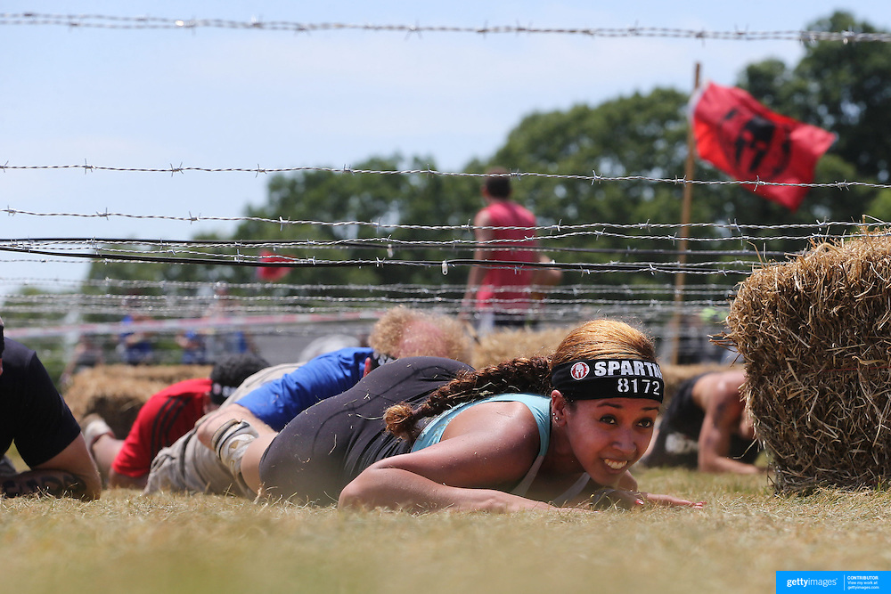 Kelly Gutierrez in action at the barbed wire crawl obstacle during the Reebok Spartan Race. Mohegan Sun, Uncasville, Connecticut, USA. 28th June 2014. Photo Tim Clayton