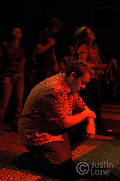 A young man is seen kneelling in prayer during Friday night services for college-age Christians at New Life Church in Colorado Springs, CO on July 8, 2005. The services are held by one of the church's youth ministries, called The Mill, and feature religous rock music, sophisticated lighting, and intense prayer.