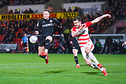 Cauley Woodrow of Barnsley (9) shoots and Andrew Butler of Doncaster Rovers (6) in action during the EFL Sky Bet League 1 match between Doncaster Rovers and Barnsley at the Keepmoat Stadium, Doncaster, England on 15 March 2019.