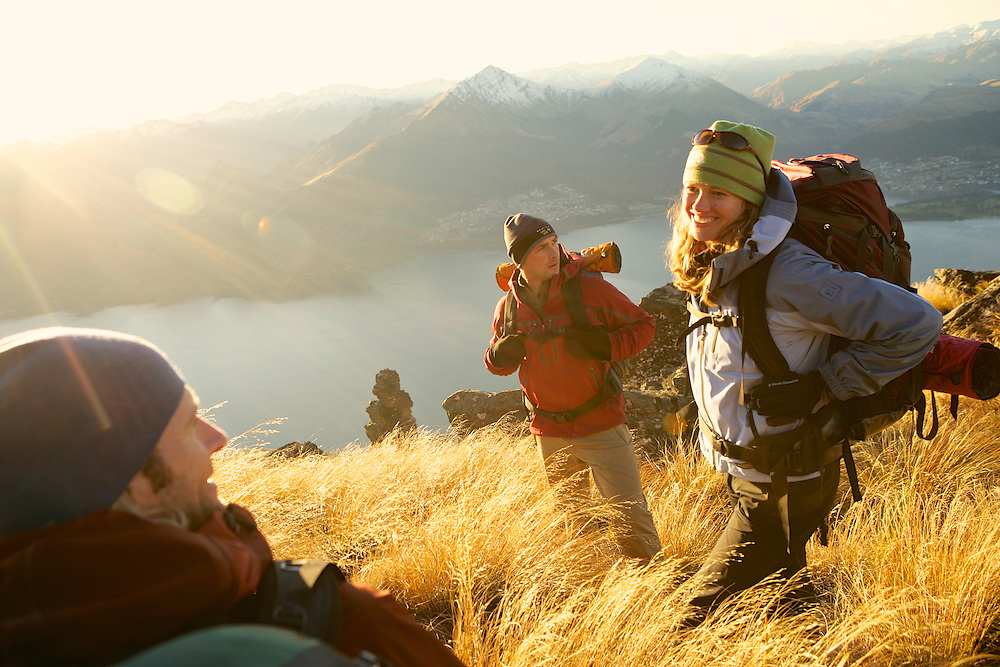 REI National Advertising in New Zealand with hikers taking a break at the ridge top at sunset with the lake and mountains in the background