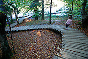 Child walking down curving wooden walkway, Plitvice National Park, Croatia