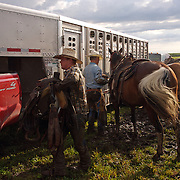 Nineteen-year-old Patrick Stark, left, and Denny Amos, unsaddle their horses following a cattle roundup at the Bar B ranch near Albia, Iowa.   During the roundup, calves were roped and seperated from the herd for vaccinations, branding and the placement of growth stimulant implants.  The male calves were also castrated.  Owner Catherine Bay runs the operation with a herd of over 2,000 cattle.