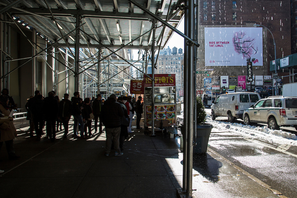 People queue to buy hot street food from Rafiqi's kiosk which is covered by temporary scaffolding on Broadway and West 31st Street intersection.  Melted snow is pouring off the roof onto the street and cars drive through snow on the road.  (photo by Andrew Aitchison / In pictures via Getty Images)