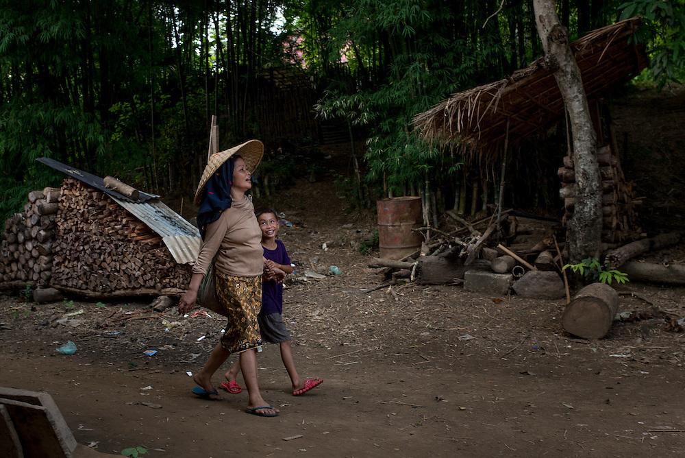 A mother and son walk through Khoc Kham village.