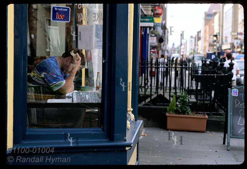 Man hunches over table with bite out of his sandwich, engrossed in reading; Baggot Street, Dublin, Ireland.