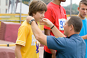 Police officer presenting medal at award ceremony. Special Olympics U of M Bierman Athletic Complex. Minneapolis Minnesota USA