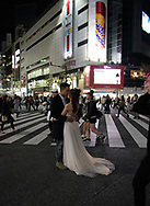 A bride in her wedding gown and groom kissing surrounded by crowds at the Shibuya crossing surrounded by neon lights in Tokyo, Honshu, Japan