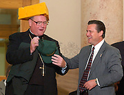 Archbishop Timothy M. Dolan holds a Green Bay Packers baseball cap and sweatshirt while wearing a cheesehead given to him by Milwaukee Alderman Robert Donovan, a member of Blessed Sacrament Parish, Milwaukee, during a visit to Milwaukee City Hall in September 2002. (Milwaukee Catholic Herald photo by Sam Lucero)
