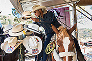 A Mexican cowboy shops for hats without getting of his horse during the annual Cabalgata de Cristo Rey pilgrimage January 6, 2017 in Guanajuato, Mexico. Thousands of Mexican cowboys take part in the three-day ride to the mountaintop shrine of Cristo Rey which concludes on the Day of Epiphany.