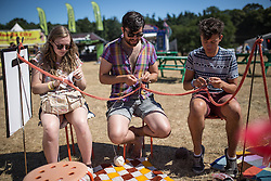 © Licensed to London News Pictures . 19/07/2013 . Suffolk , UK . People enjoy knitting in the sunshine at The Latitude music and culture festival in Henham Park , Southwold . Photo credit : Joel Goodman/LNP