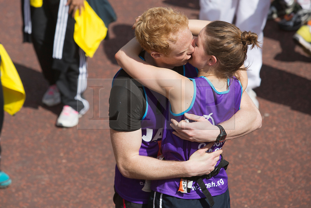 © Licensed to London News Pictures. 21/04/2013. London, England. Picture: James Carmel has his marriage proposal accepted by Lianne Humphrey. Picture: Celebrity Runners and Fun Runners finish the Virgin London Marathon 2013 race in the Mall, London. Many wore black ribbons to pay their respect for those who died or were injured in the Boston Marathon. Photo credit: Bettina Strenske/LNP