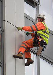 © Licensed to London News Pictures. 27/06/2017. London, UK. A specialist measures a cladding panel as he abseils down the face of Bray tower on the Chalcots Estate in Camden after it failed a fire inspection because of combustable cladding. More than 700 flats in tower blocks on an estate in the Swiss Cottage area of north-west London are being evacuated because of fire safety concerns after the Grenfell Tower fire of on June 14. Photo credit: Peter Macdiarmid/LNP
