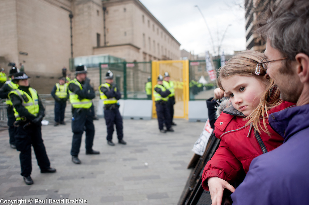 "demonstrator with young child leans against ""the ring of steel""  and watches police in  Barkers Pool, outside Sheffield city Hall where the Liberal Democrats are holding their Party conference Conference Sheffield Saturday.12 March 2011.Images © Paul David Drabble"