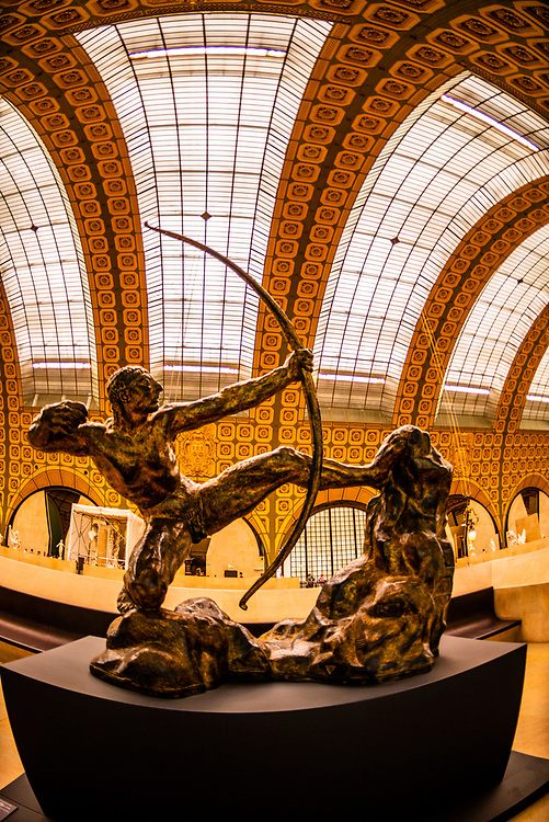 """Gilded bronze statue """"Hercules the Archer"""" aka """"Hercules Killing the Birds of Lake Stymphalis"""" by Emile-Antoine Bourdelle, Musee d""""Orsay,  a museum in Paris, France, on the Left Bank of the Seine. It is housed in the former Gare d'Orsay, a Beaux-Arts railway station built between 1898 and 1900."""