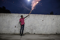 RIO DE JANEIRO, BRAZIL - JANUARY 24: A young man shoots a firework at the start of a candomble ceremony, in Rio de Janeiro, Brazil, on Saturday, Jan. 23, 2015. Brazil's Afro-Brazilian religions which in recent years have come under increasing threats and prejudice, particularly from the growing number of evangelical churches. Candombl&eacute; originated in Salvador, Bahia at the beginning of the 19th century when enslaved Africans brought their beliefs with them. Umbanda and candombl&eacute; are Afro-Brazilian religions practiced in mostly Brazil. <br /> (Lianne Milton for the Washington Post)