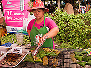 25 JUNE 2011 - SANPATONG, THAILAND: A vendor grills sticky rice and bananas wrapped in banana leaf at the Sanpatong buffalo market near Chiang Mai, Thailand, June 25. The buffalo market in Sanpatong started as a weekly gathering of farmers and traders buying and selling water buffalo, the iconic beast of burden in Southeast Asia, more than 60 years ago and has grown into one of the largest weekend markets in northern Thailand. Buffalo and cattle are still a main focus of the market, but traders also buy and sell fighting cocks, food, clothes, home brew and patent medicines.   PHOTO BY JACK KURTZ
