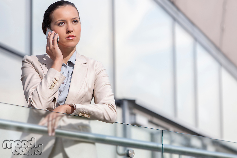 Serious young businesswoman using smart phone at office railing