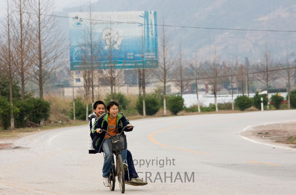 Boys riding on a bicycle on empty road near Guilin, China