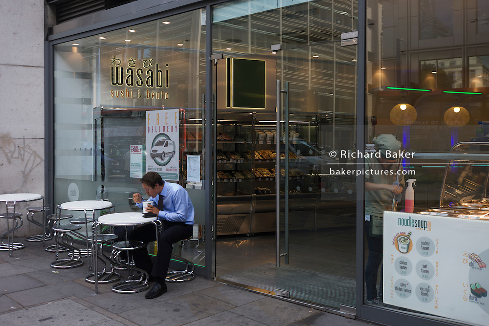 Man slurps noodles from a pot outside City of London Sushi shop while woman employee cleans surfaces inside store.