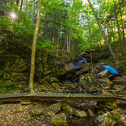 A man rides his mountain bike over a bridge on a trail on Mount Ascutney in West Windsor, Vermont.