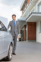 Full-length of businessman standing by car outside hotel