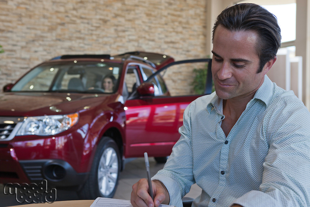 Man signing papers with car in background